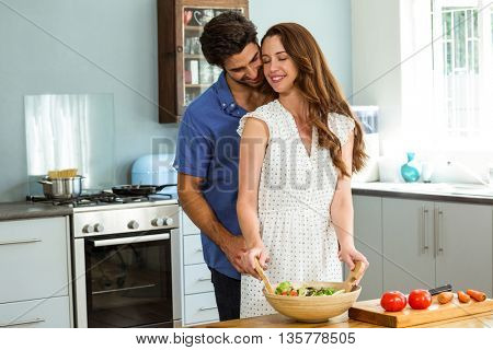 Young couple embracing while mixing a salad in kitchen