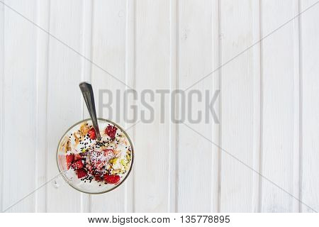 top view icecream in a cup with strawberry pistachio coconut