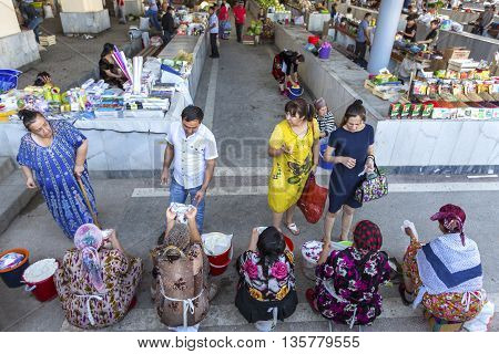 SAMARKAND, UZBEKISTAN - MAY 18, 2016: Women shop and negotiate to buy cheese in the Siab Bazaar.