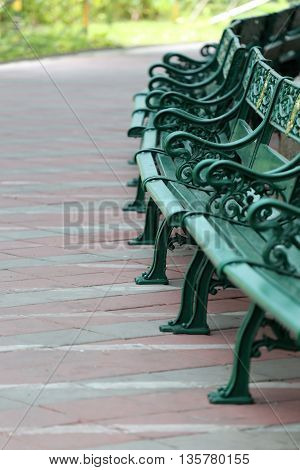 Green benches in the public park equipment furniture of decorate garden for relaxing.