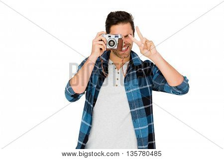 Man photographing with camera and making v sign on white background