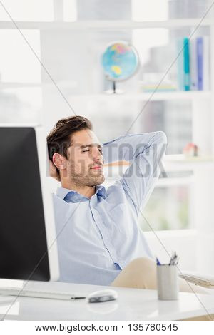 Relaxed businessman sitting with hands behind head in the office