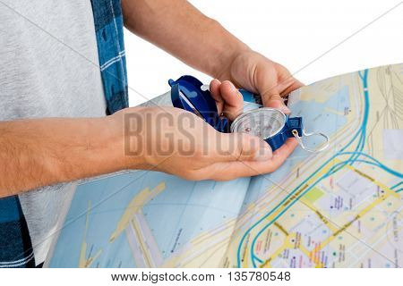 Close-up of man holding map and compass on white background