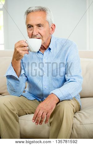 Senior man drinking coffee while sitting on sofa at home