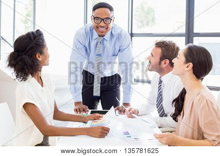 Business people sitting and discussing a report in office