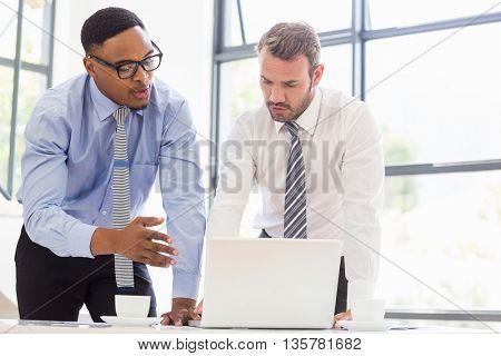 Businessmen using laptop at desk in office