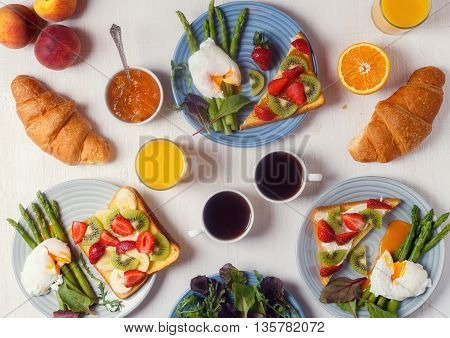 Table with breakfast - asparagus with poached eggs toast with fruit croissants coffee juice top view.