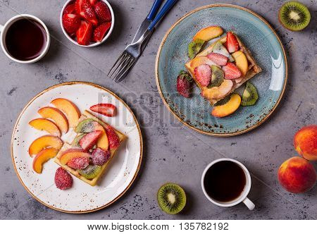 Breakfast waffles with fresh fruit on the concrete surface top view.