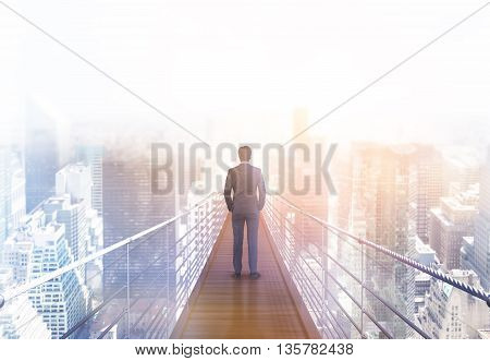 Business risk and research concept with back view of businessman standing on suspended bridge above New York city and looking into the distance. Toned image 3D Rendering