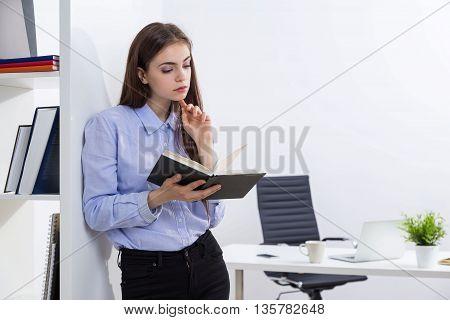 Businesswoman Going Through Notepad