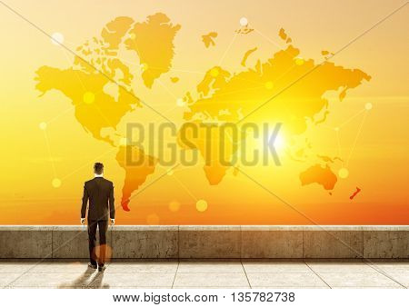 Global network concept with businessman looking at abstract map with network at sunrise