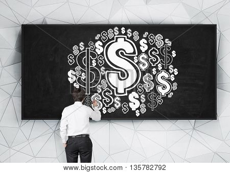 Businessman drawing abstract dollar sign sketch on chalkboard hanging on patterned wall
