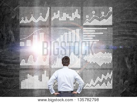 Businessman looking at business charts on grid. Concrete wall background