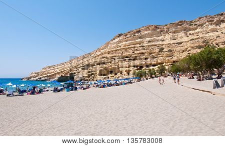 CRETE GREECE-JULY 22: Holidaymakers on Matala beach with the caves on July 222014 Crete island Greece.