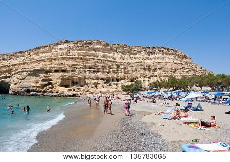 CRETE GREECE-JULY 22: Holidaymakers on Matala beach with the caves on Libyan sea on July 222014 Crete Greece.