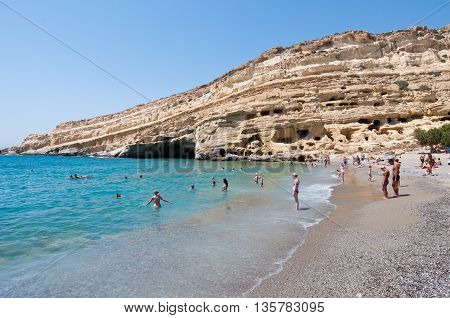 CRETE GREECE-JULY 22: Tourists on Matala beach with the caves on Libyan sea on July 222014 Crete Greece.