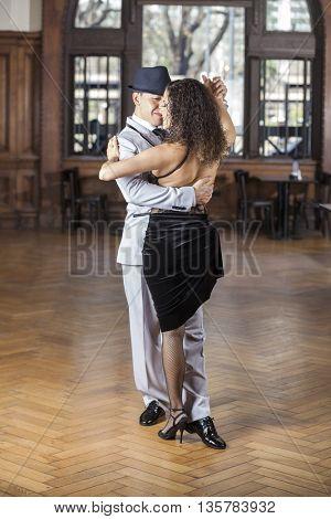 Dancers Performing Tango On Hardwood Floor In Restaurant