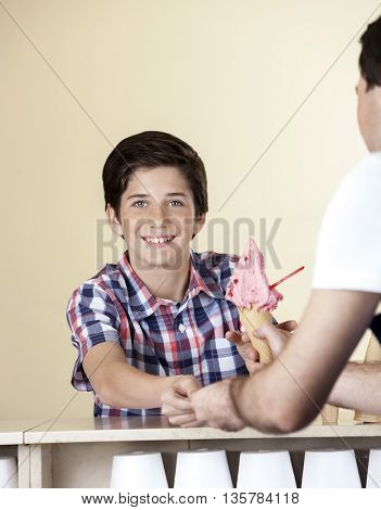 Happy Boy Paying For Strawberry Ice Cream To Waiter