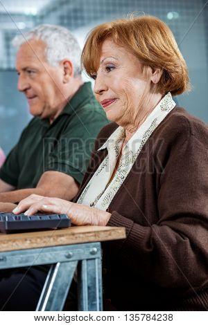 Confident Senior Students Using Computer In Classroom
