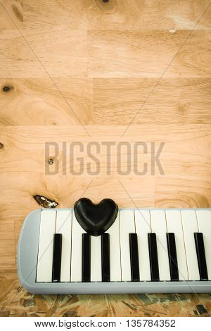 Still life with black heart and melodian on wooden background