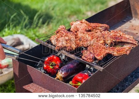 Grilled beef fillet ribs on bbq over charcoal. Roasted meat. Large pieces of grilled meat during cooking. Veal on the bone. The man flips the meat with tongs.