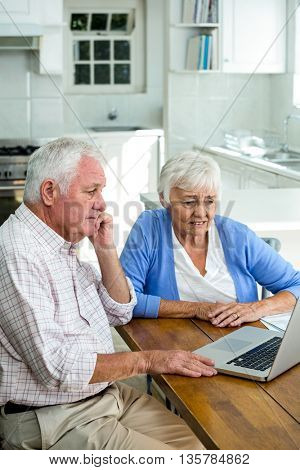 Serious retired couple using laptop while sitting at home