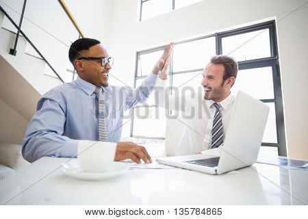 Businessmen giving a high five while at a meeting in office