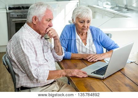 Serious senior couple using laptop while sitting at home