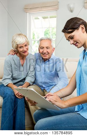 Consultant holding clipboard with senior couple while sitting on sofa at home