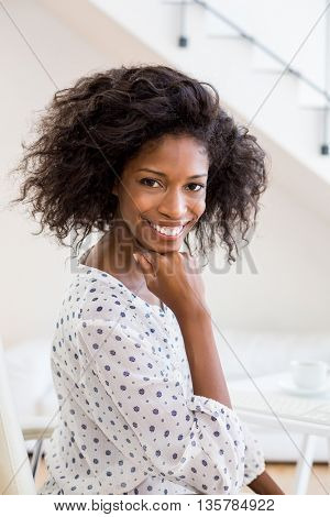 Portrait of happy businesswoman with hand on chin in office