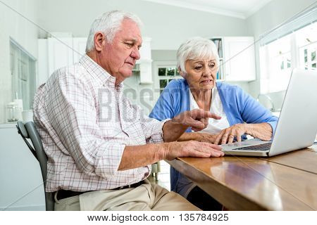 Serious retired man pointing at laptop while sitting at home