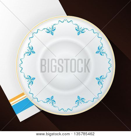White plate with a blue pattern and a gold border on a white towel