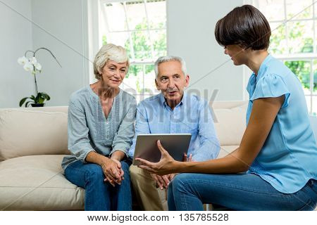 Female consultant showing digital tablet to aged couple while sitting on sofa