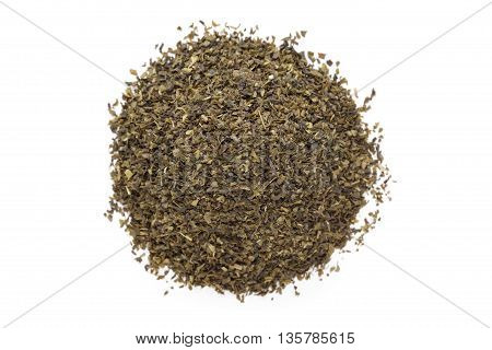 Organic Green tea (Camellia sinensis) Tea bag cut, dried leaves, isolated on white background. Macro close up. Top view.