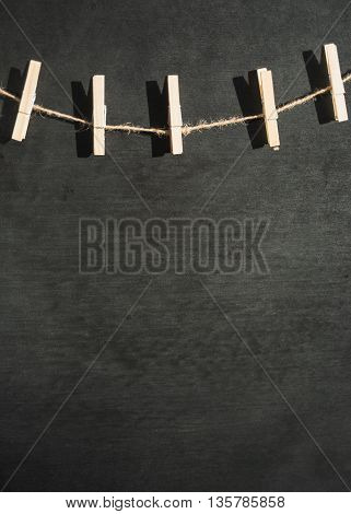 wooden clothespins on a twine on black slate