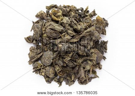 Organic Green Tea (Camellia sinensis) dried whole leaves isolated on white background. Macro close up. Top view.