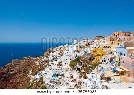 Colorful Oia village on the edge of the caldera cliffs with windmills in the distance on the island of Thira (Santorini) Greece.