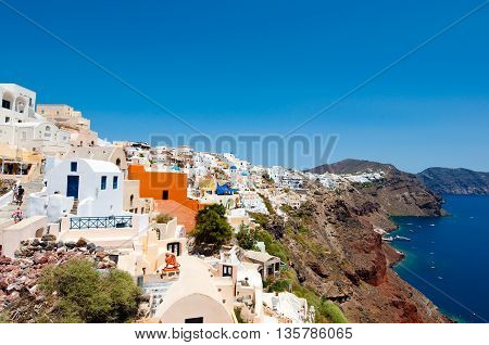 Oia traditional architecture with whitewashed buildings carved into the rock on the edge of the caldera cliff on the island of Thira (Santorini) Greece.