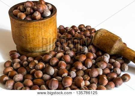 Hazelnuts and wooden pestle on a white background