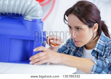 beautiful woman fixing ventilation parts with screwdriver