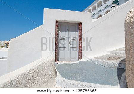 Entrance to the house carved into the rock on the edge of the caldera cliff in Fira town. Thira (Santorini) Greece.