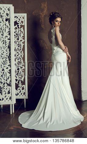 beautiful young bride in classy dress, posing in indoor