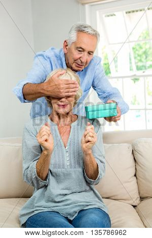 Senior man giving surprise to man by gifting at home