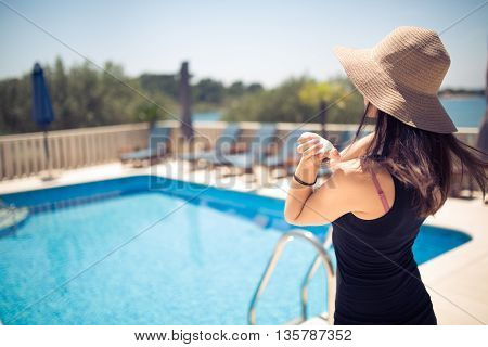 Young fashionable woman posing in a black dress while entering the pool.Beautiful sexy young woman with perfect slim figure with long dark hair. Girl enjoying her summer vacation. Luxury lifestyle.