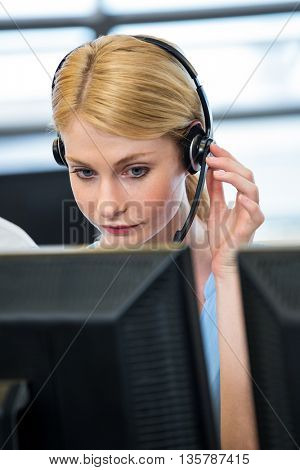 Woman working on computer with headset in office