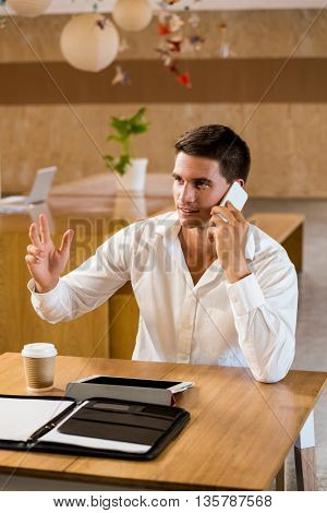 Man talking on mobile phone in office