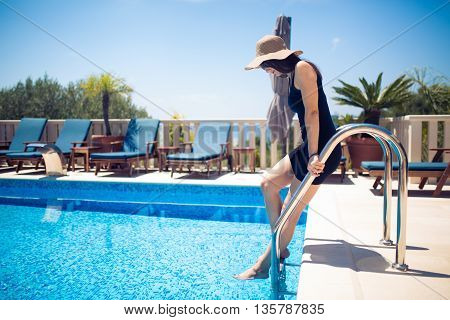 Young fashionable woman in black dress enjoying her vacation in villa beside the pool.Summer vacation,seaside villa house.Europe summer holiday.Pool party.Croatia vacation