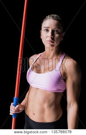 Female athlete holding a javelin on black background
