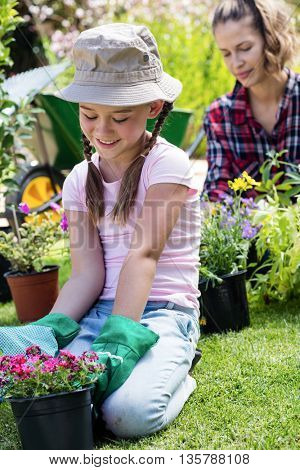 Girl sitting in garden with flower pot while mother gardening in background