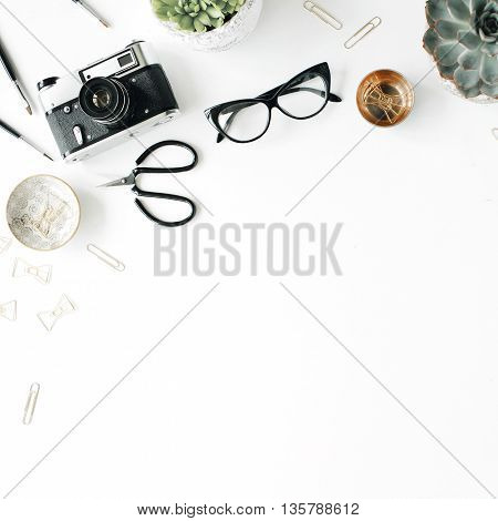 feminini desk workspace with succulent retro camera scissors glasses and golden clips on white background. flat lay top view